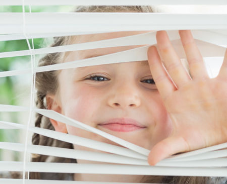 girl-peeking-through-window-blinds